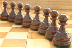Pawns. Wooden pawns on a wooden board stock images