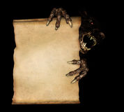 Paws of a monster holding a vintage scroll Royalty Free Stock Image