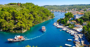 Paxos island panorama with boat entering the grand canal Royalty Free Stock Images