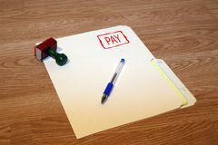 Pay. Office series with stamp and pad on desk with folder and pen. Room for text or logo royalty free stock photography