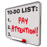 Pay Attention Message Board Attentive Conscious Awareness. Pay Attention words written on a dry erase board telling you to watch, listen, be attentive and Royalty Free Stock Image