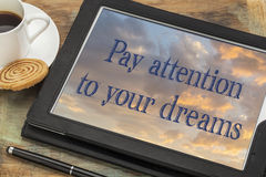 Pay attention to your dreams. Inspirational text on a digital tablet with a cup of coffee Stock Photos