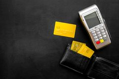 Pay by bank card, pay by credit card. Payment terminal near card and wallet with bank and credit cards on black royalty free stock images