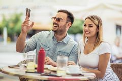 Pay the bill. Attractive young couple holding credit card while siting in sidewalk cafe stock images