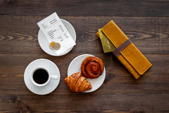 Pay bill at cafe by card. Purse, bill and bank card near coffee and croissant on dark wooden table top view Stock Images