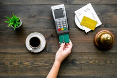 Pay the bill by payment terminal. Woman`s hand insert bank card in payment terminal near bill, service bell, coffee and. Donuts on dark wooden background top royalty free stock image