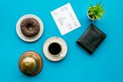 Pay the bill, pay at restaurant. Check near wallet, service bell, coffee on blue background top view.  stock photos