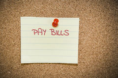 Pay bills note on a bulletin board Royalty Free Stock Photos