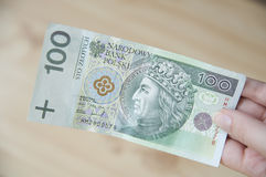 Pay in cash. Hand with a one hundred zloty bill Stock Photos