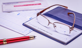 Pay with check instantly, on time. Glasses on a checkbook, red pen, financial documents on the background. Closeup, financial conc. Glasses on a checkbook, red royalty free stock photos