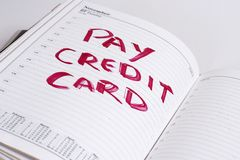 Pay credit card bill. An open desk top diary with a big red reminder to pay a credit card bill Stock Image