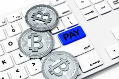 Pay, cryptocurrency and payment concept. Close up of white keyboard with blue button and silver bitcoins. Pay, cryptocurrency and payment concept. 3D Rendering Stock Photography