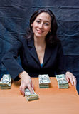 Pay day. Happy smiling business woman paying ourt money isolated on a dark background stock image