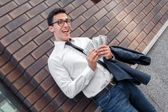 Pay day. Businessman in eyeglasses leaning on wall on the city street holding salary smiling playful stock photography