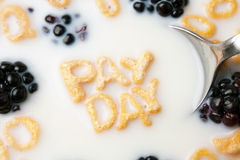 Pay Day Cereal Letters. The words PAY DAY spelled out of letter shaped cereal pieces floating in a milk filled cereal bowl Royalty Free Stock Image