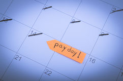 Pay day written on sticky note, calendar. Stock Images