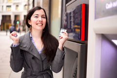 Pay day. Young woman celebrating at the cash machine Royalty Free Stock Photos