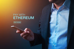 Pay with Ethereum cryptocurrency. Concept with businessman and electronic device Stock Photography