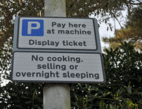 Pay here at machine sign. Pay here machine sign that's states no cooking or selling or overnight sleeping Royalty Free Stock Image