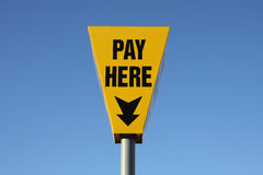 Pay Here Sign. A bright yellow sign in a car park set against a blue sky Stock Photography