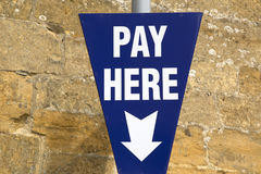 Pay Here Sign. Against Stone Wall Royalty Free Stock Photos