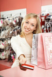 Pay off with a card for purchases. The woman stretches forward a card for payment of purchases at a counter Stock Image