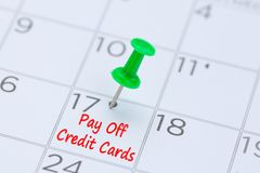 Pay Off Credit Cards written on a calendar with a green push pin. To remind you and important appointment Royalty Free Stock Photo