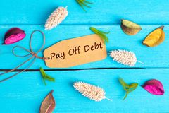 Pay off debt text on paper tag. With rope and color dried flowers around on blue wooden background royalty free stock photos