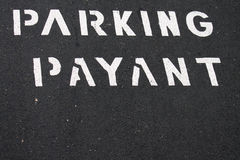 Pay for parking in french. Close up of text in french for payable parking on grey asphalt floor Stock Photos