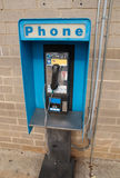 Pay phone. A pay phone by a brick wall stock photo