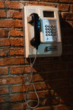 Pay phone on the red brick wall Royalty Free Stock Photography