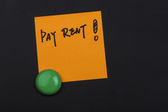 Pay rent note on blackboard. Close up of a post-it note saying pay rent on blackboard background Royalty Free Stock Image