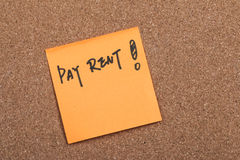 Pay rent note. Close up of a post-it note saying pay rent Stock Images