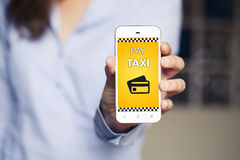 Pay Taxi message on a mobile phone screen. Woman holding smartph Stock Images