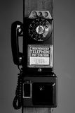 Pay telephone with dial. Antigue pay telephone with dial mounted on a wooden pole royalty free stock photography