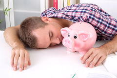 Pay tuition fees. From the piggy bank. Tired young student laying on desk with savings Royalty Free Stock Photos