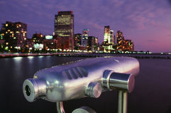 Pay View Telescope and Night View of the City. Coin operated telescope for sightseeing against the water and downtown buildings at night. Horizontal shot Royalty Free Stock Images