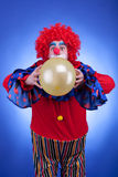 Payaso con el globo en traje rojo en fondo azul Foto de archivo