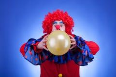 Payaso en traje rojo con el globo en manos Fotografía de archivo