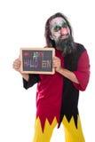 Payaso espeluznante que lleva a cabo una muestra, feliz Halloween colorido del texto, aislador foto de archivo libre de regalías