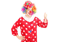 Payaso feliz sonriente en el traje rojo que da el pulgar para arriba Imagen de archivo libre de regalías