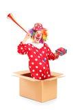 Payaso juguetón que sale de una caja y que sostiene un cuerno y un prese Fotografía de archivo