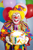 Payaso loco con la torta de cumpleaños Imagenes de archivo