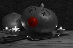 Payaso negro y blanco de la calabaza con un cuchillo Imagenes de archivo