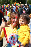 Payaso no identificado de la muchacha que detiene a un niño lindo y que presenta en el carnaval anaranjado del flor Imagen de archivo
