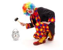 Payaso que golpea el reloj de alarma con el martillo Imágenes de archivo libres de regalías