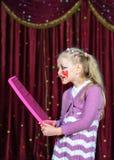 Payaso que lleva Make Up Holding de la muchacha sobre el peine clasificado Foto de archivo