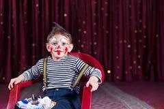 Payaso que lleva Makeup Sitting del muchacho en silla en etapa Imágenes de archivo libres de regalías