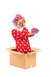 Payaso sonriente en una caja de cartón que sostiene un regalo Imagen de archivo libre de regalías