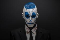 Payaso terrible y tema de Halloween: Payaso azul loco en el traje negro aislado en un fondo oscuro en el estudio Fotografía de archivo